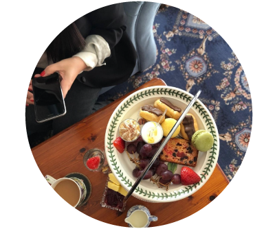 Woman holds phone ready to capture here afternoon tea selection at home