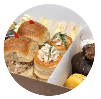 Afternoon Tea Dublin Chicken Brioche Sandwich, Egg and Cress Sandwich and Salmon and Cream Cheese Vol au vent in box Close up