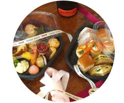 Take-away boxes of Afternoon Tea sandwiches, scones, miniature cakes and a bottle of prosecco