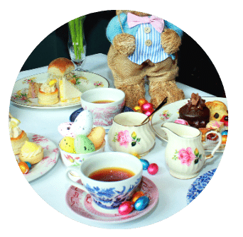Easter Afternoon Tea spread out on pretty plates with floral jug and Easter bunny