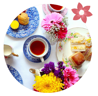 cup of bombay chai organic tea in cup surrounded by sandwiches scones and flowers