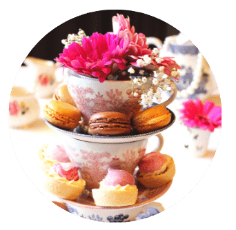 Macaroons on saucers stacked with tea cups and flowers for Mothers Day Afternoon Tea at Home Old Music Shop Restaurant Dublin