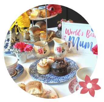 Worlds Best Mum card beside jug, sugar bowl and afternoon tea stand with cakes sandwiches and scones on plates. flowers in vases and pearls around tea cups
